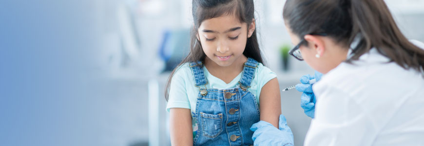 A clinician administers a vaccine to a child