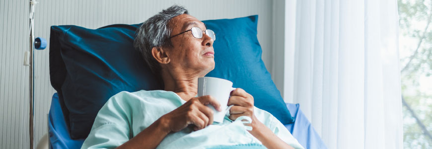 An older adult man laying in hospital bed