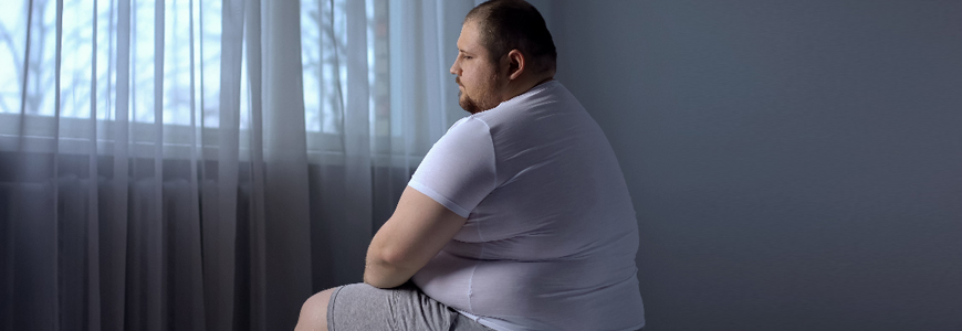 Obese white man looking out a window