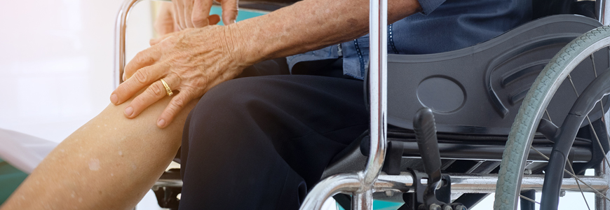 Patient in a wheelchair touching knee