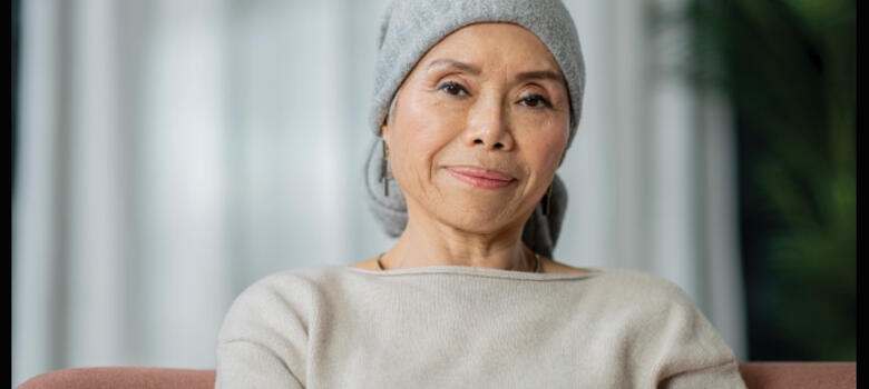 A woman with cancer wearing a head covering
